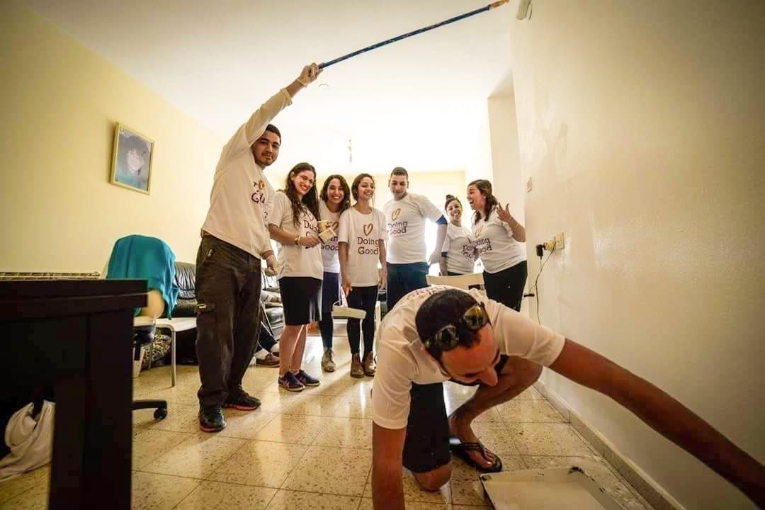 Photo of Arab volunteers helping the Holocaust survivors to paint their houses